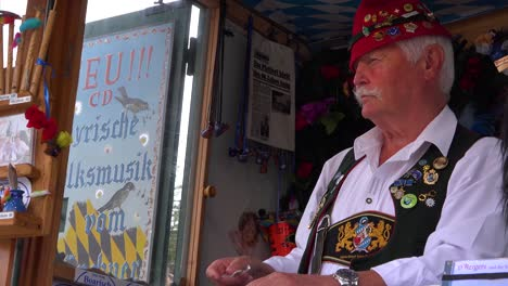 A-carnival-barker-in-a-booth-makes-bird-noises-for-passersby-at-Oktoberfest-in-Germany