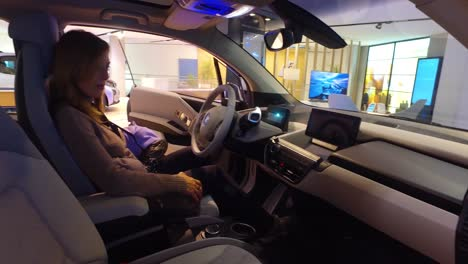 A-woman-sits-in-a-BMW-sedan-in-a-showroom