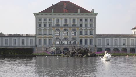 Swans-move-across-a-pond-in-front-of-Nymphenburg-Palace-in-Munich-Germany-1