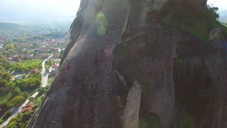 Beautiful-aerial-as-climbers-ascend-a-sheer-rocky-cliff-face-in-Meteora-Greece