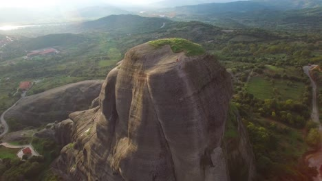 Beautiful-aerial-as-climbers-summit-a-sheer-rocky-cliff-face-in-Meteora-Greece