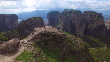 Beautiful-aerial-over-two-people-taking-photos-atop-the-rock-formations-of-Meteora-Greece