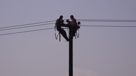 Two-men-in-silhouette-work-on-an-electrical-cable-atop-a-telephone-pole
