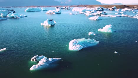 Drone-aerial-over-icebergs-moving-in-a-glacial-bay-Jokulsarlon-glacier-lagoon-Iceland-suggesting-global-warming-1