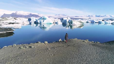 Aerial-of-a-woman-standing-along-the-shore-of-a-glacier-lagoon-in-the-Arctic-at-Jokulsarlon-glacier-lagoon-Iceland-1