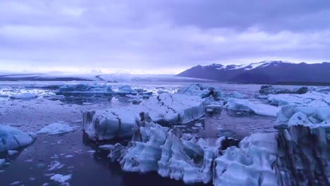 Drone-aerial-over-icebergs-in-a-glacial-bay-suggest-global-warming-in-the-Arctic-at-Jokulsarlon-glacier-lagoon-Iceland-night-1