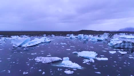 Drone-aerial-over-icebergs-in-a-glacial-bay-suggest-global-warming-in-the-Arctic-at-Jokulsarlon-glacier-lagoon-Iceland-night-3