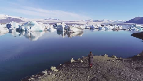 Aerial-of-a-woman-standing-along-the-shore-of-a-glacier-lagoon-in-the-Arctic-at-Jokulsarlon-glacier-lagoon-Iceland-4