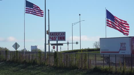 A-long-distance-trucker-passes-a-budget-hotel-and-american-flags-along-a-US-interstate-highway-in-America