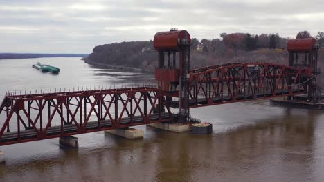 Drone-aerial-footage-of-a-drawbridge-on-the-Mississippi-slowly-opening-to-make-way-for-a-huge-barge-traveling-upstream