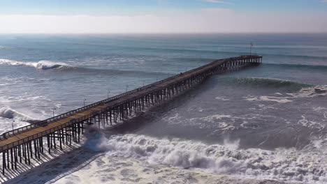 Aerial-over-huge-waves-rolling-in-over-a-California-pier-in-Ventura-California-during-a-big-winter-storm-suggests-global-warming-and-sea-level-rise-or-tsunami
