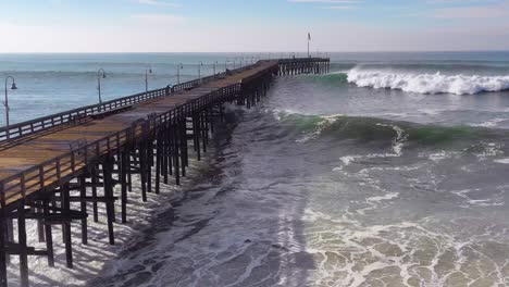 Aerial-over-huge-waves-rolling-in-over-a-California-pier-in-Ventura-California-during-a-big-winter-storm-suggests-global-warming-and-sea-level-rise-or-tsunami-1