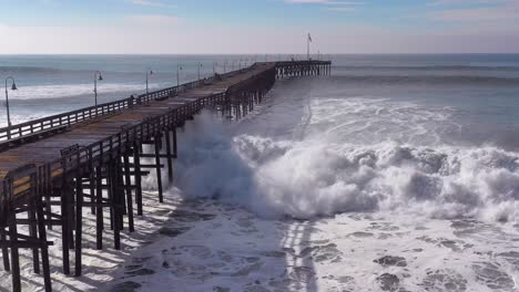 Aerial-over-huge-waves-rolling-in-over-a-California-pier-in-Ventura-California-during-a-big-winter-storm-suggests-global-warming-and-sea-level-rise-or-tsunami-2