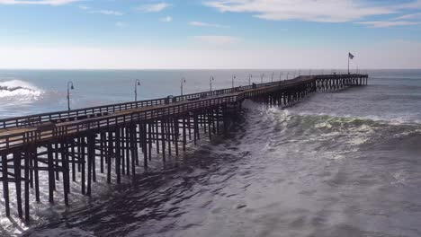 Aerial-over-huge-waves-rolling-in-over-a-California-pier-in-Ventura-California-during-a-big-winter-storm-suggests-global-warming-and-sea-level-rise-or-tsunami-3