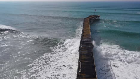 Aerial-over-huge-waves-rolling-in-over-a-California-pier-in-Ventura-California-during-a-big-winter-storm-suggests-global-warming-and-sea-level-rise-or-tsunami-8