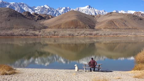 A-man-and-his-dog-enjoy-a-beautiful-day-at-a-lake-at-the-base-of-Mt-Whitney-and-the-Sierra-Nevada-mountains-near-Lone-Pine-California
