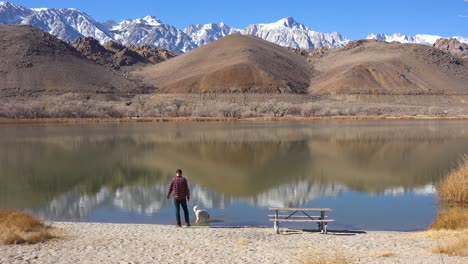 A-man-and-his-dog-enjoy-a-beautiful-day-at-a-lake-at-the-base-of-Mt-Whitney-and-the-Sierra-Nevada-mountains-near-Lone-Pine-California-1