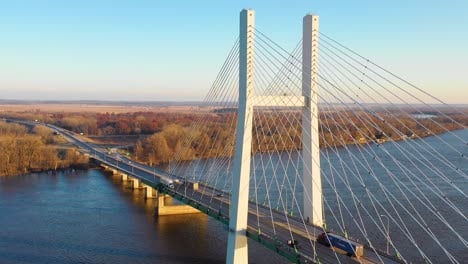 A-drone-aerial-of-trucks-crossing-a-bridge-over-the-Mississippi-River-at-Burlington-Iowa-suggesting-infrastructure-shipping-trucking-or-transportation
