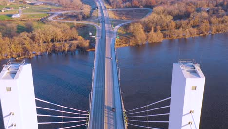 A-drone-aerial-of-cars-and-trucks-crossing-a-bridge-over-the-Mississippi-River-at-Burlington-Iowa-suggesting-infrastructure-shipping-trucking-or-transportation-1