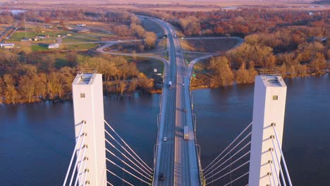 A-drone-aerial-tilt-down-follows-a-commercial-truck-crossing-a-bridge-over-the-Mississippi-River-at-Burlington-Iowa-suggesting-infrastructure-shipping-trucking-or-transportation