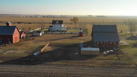 A-drone-aerial-establishing-shot-of-a-classic-farmhouse-farm-and-barns-in-rural-midwest-America-York-Nebraska