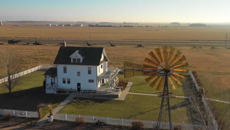 A-high-angle-establishing-shot-of-a-classic-farmhouse-farm-and-barns-in-rural-midwest-America-York-Nebraska