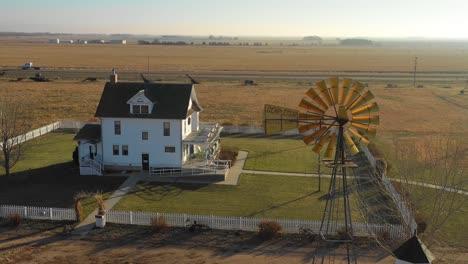A-drone-aerial-establishing-shot-of-a-classic-farmhouse-farm-and-barns-in-rural-midwest-America-York-Nebraska-1