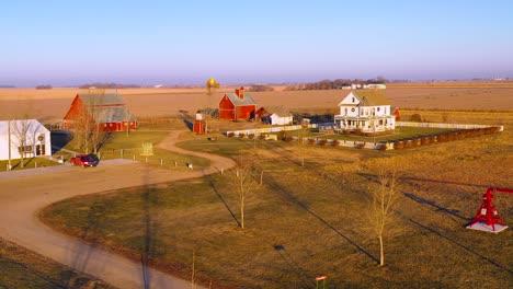 A-drone-aerial-establishing-shot-over-a-classic-farmhouse-farm-and-barns-in-rural-midwest-America-York-Nebraska