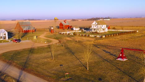 A-drone-aerial-establishing-shot-over-a-classic-farmhouse-farm-and-barns-in-rural-midwest-America-York-Nebraska-1
