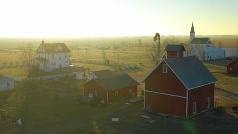 A-drone-aerial-at-dawn-establishing-shot-over-a-classic-farmhouse-farm-and-barns-in-rural-midwest-America-York-Nebraska