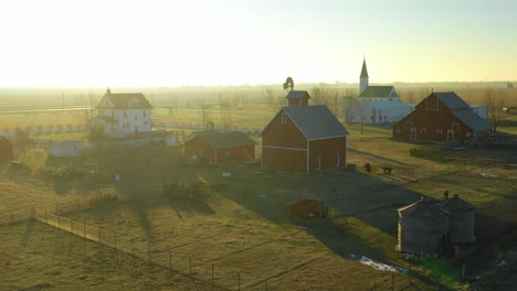 A-drone-aerial-at-dawn-establishing-shot-over-a-classic-farmhouse-farm-and-barns-in-rural-midwest-America-York-Nebraska-1
