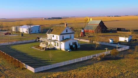 A-drone-aerial-establishing-shot-over-a-classic-beautiful-farmhouse-farm-and-barns-in-rural-midwest-America-York-Nebraska