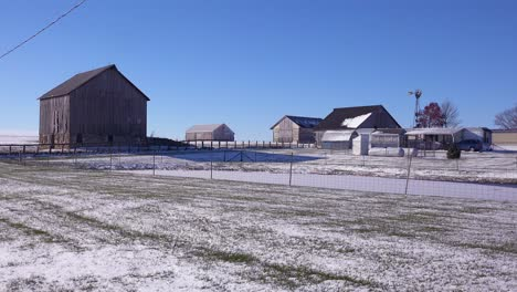 Establishing-shot-of-a-classic-beautiful-small-town-farmhouse-farm-and-barns-in-rural-midwest-America-in-winter-snow