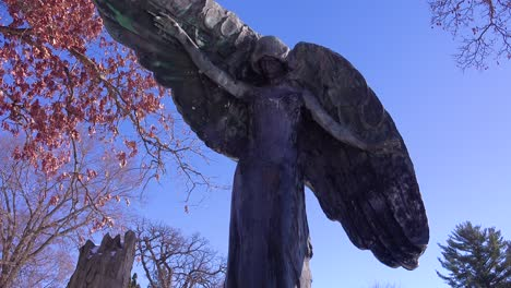 A-spooky-Halloween-giant-angel-statue-guards-a-cemetery-or-graveyard-in-this-haunted-image
