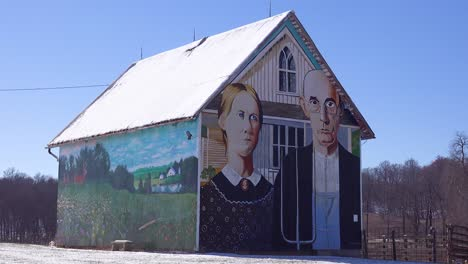 A-rural-barn-has-a-rendition-of-Grant-Wood-s-American-Gothic-painting-on-the-side