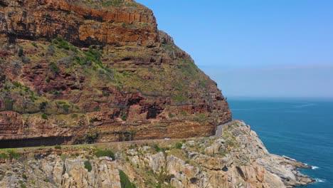 Una-Toma-Aérea-De-Un-Automóvil-Que-Viajaba-Por-Una-Peligrosa-Y-Estrecha-Carretera-De-Montaña-A-Lo-Largo-Del-Océano-Chapmans-Peak-Road-Cerca-De-Ciudad-Del-Cabo-Sudáfrica