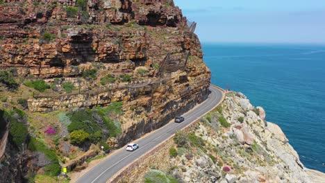 An-vista-aérea-shot-of-cars-traveling-on-a-dangerous-narrow-montaña-road-along-the-ocean-Chapmans-Peak-Road-near-Cape-Town-South-Africa