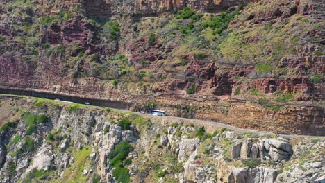 An-vista-aérea-shot-of-a-bus-and-cars-traveling-on-a-dangerous-narrow-montaña-road-along-the-ocean-Chapmans-Peak-Road-near-Cape-Town-South-Africa