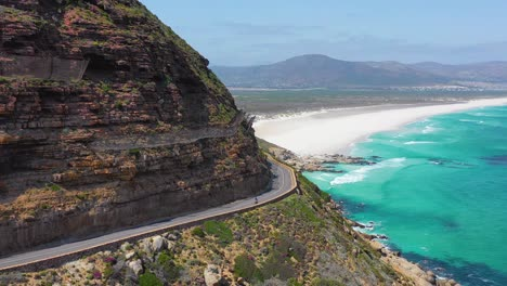 An-aerial-shot-of-a-bicyclist-traveling-on-a-dangerous-narrow-mountain-road-along-the-ocean-Chapmans-Peak-Road-near-Cape-Town-South-Africa-1