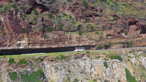 An-aerial-shot-of-a-car-traveling-on-a-dangerous-narrow-mountain-road-along-the-ocean-Chapmans-Peak-Road-near-Cape-Town-South-Africa-1