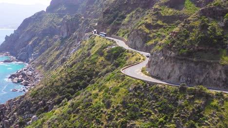 An-vista-aérea-shot-of-a-convoy-of-busses-traveling-on-a-dangerous-narrow-montaña-road-along-the-ocean-Chapmans-Peak-Road-near-Cape-Town-South-Africa