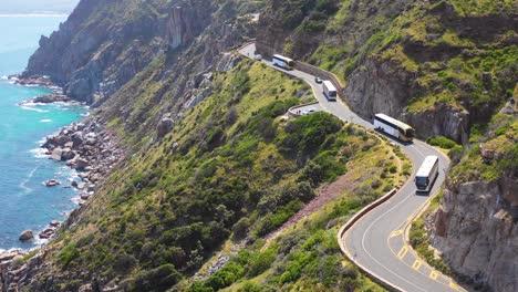 Una-Toma-Aérea-De-Un-Convoy-De-Autobuses-Que-Viajan-Por-Una-Peligrosa-Carretera-De-Montaña-Estrecha-A-Lo-Largo-Del-Océano-Chapmans-Peak-Road-Cerca-De-Ciudad-Del-Cabo-Sudáfrica-1