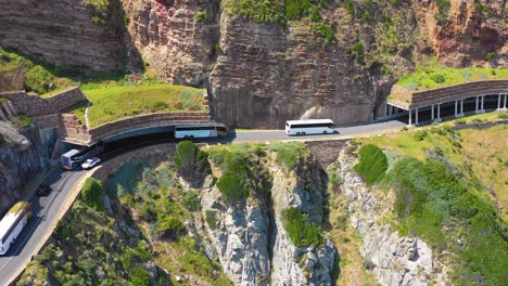 An-aerial-shot-of-a-convoy-of-busses-traveling-on-a-dangerous-narrow-mountain-road-along-the-ocean-Chapmans-Peak-Road-near-Cape-Town-South-Africa-2