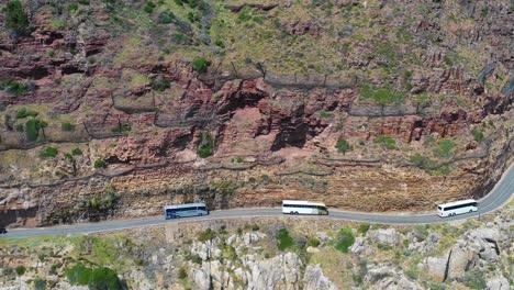 Eine-Luftaufnahme-Eines-Buskonvois-Der-Auf-Einer-Gefährlichen-Schmalen-Bergstraße-Entlang-Der-Ocean-Chapmans-Peak-Road-In-Der-Nähe-Von-Kapstadt-Südafrika-Fährt-3-South