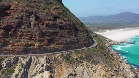 An-aerial-shot-of-a-car-traveling-on-a-dangerous-narrow-mountain-road-along-the-ocean-Chapmans-Peak-Road-near-Cape-Town-South-Africa-2