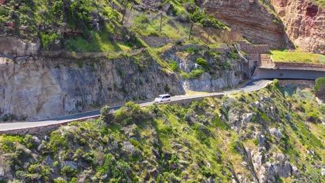 An-aerial-shot-of-a-car-minivan-traveling-on-a-dangerous-narrow-mountain-road-along-the-ocean-Chapmans-Peak-Road-near-Cape-Town-South-Africa