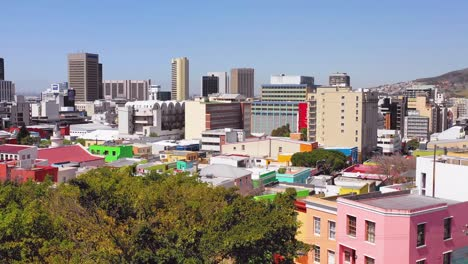 Aerial-over-treetops-reveals-colorful-Bo-kaap-Cape-Town-neighborhood-and-downtown-city-skyline