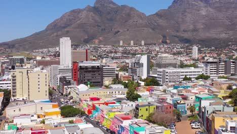 Tilt-down-aerial-reveals-colorful-Bo-kaap-Cape-Town-neighborhood-and-downtown-city-skyline
