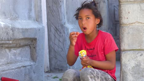 A-young-girl-eats-snacks-in-the-colorful-Bo-kaap-Malay-area-of-Cape-Town-South-Africa-with-colonial-buildings-and-traffic