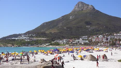 Establishing-shot-of-a-beautiful-busy-holiday-beach-scene-at-Camps-Bay-Cape-Town-South-Africa-with-Lions-Head-peak-background-1